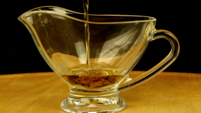 Vinegar is poured into a gravy boat video