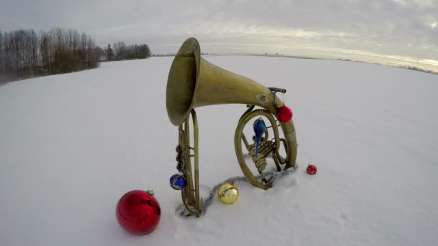 Vintage brass musical instruments on snow with Christmas decorations, time lapse video