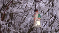 Vintage Christmas ornament hanging on hoarfrost covered shrub branch video