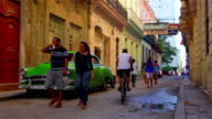 Vintage green car parked in the Habana Vieja district with people walking around video