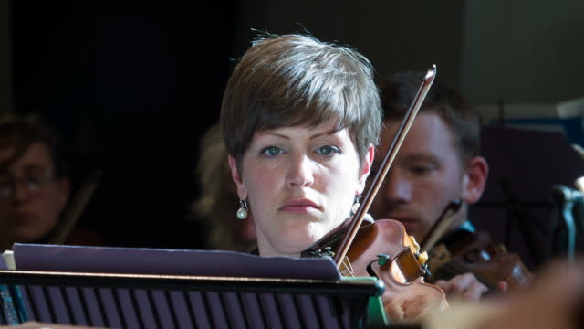 Violinist playing in a symphony orchestra video