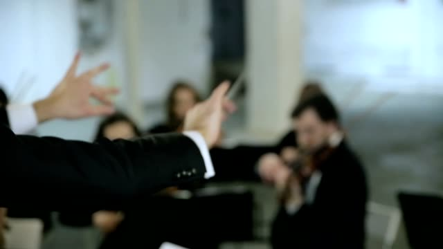 Violinists and conductor playing music video