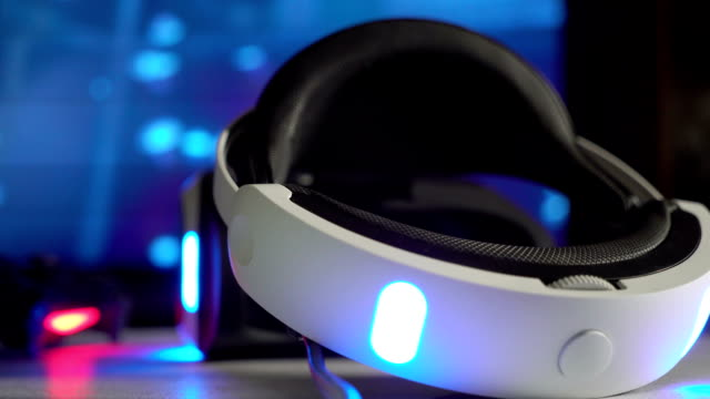 Virtual reality VR headset and wireless gaming controller in front of TV screen video