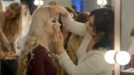 Visage master does professional make up, attractive beautiful caucasian woman gets ready for photoshooting video