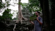 Visitor get bored with guide in Ta Prohm temple, angkor video