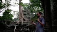 Visitor reading tourist information map in Ta Prohm temple, angkor video