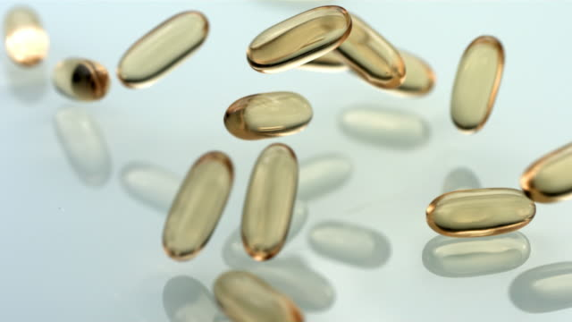 Vitamins falling on reflective surface, slow motion video