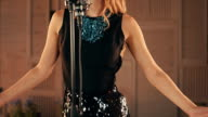 Vocalist in glowing dress perform on stage at microphone. Raise hands. Dance video