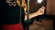 Vocalist in red dress elegantly dancing at microphone. Retro style. Click finger video