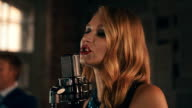 Vocalist with red lips perform on stage at concert microphone. Retro style video