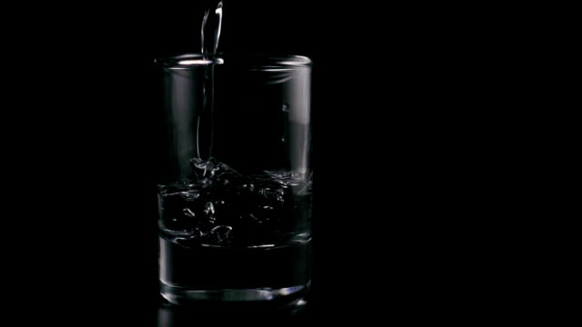 Vodka, a clear liquid is poured into a shot on a black background. Slow mo video