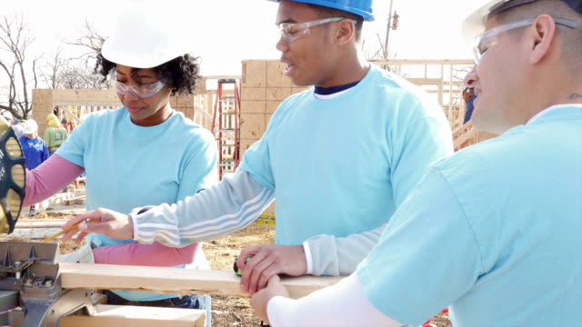 Volunteer construction foreman teaching woman how to use miter saw video