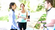 Volunteer greeting mother and daughter team as they register for marathon race video