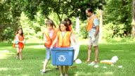 Volunteers: Family cleans up their community park. Recycling bin. video