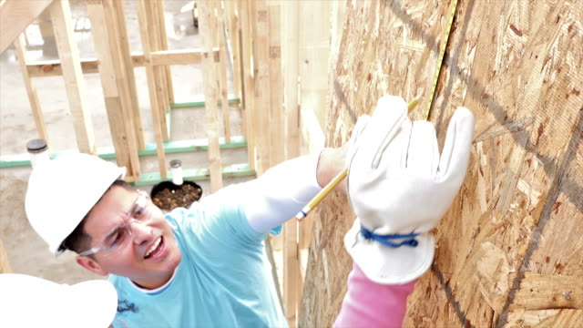 Volunteers measure plywood as they help build home for charity video