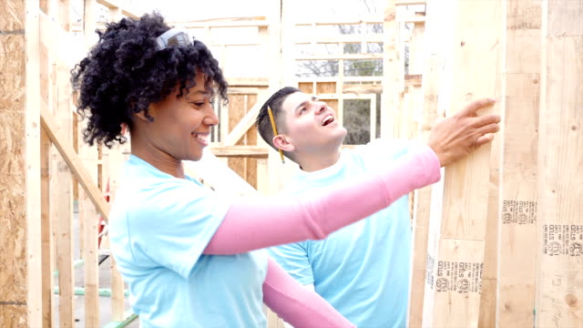Volunteers work on construction frame on home being built for charity video
