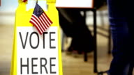 'Vote Here' sign. People walking in, out of polling station. video