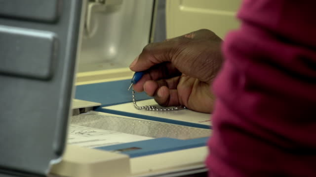 Voting, close up of hands punching ballot video
