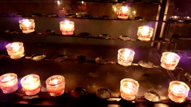 Votive candles lit in some cathedral and standing on some low racks video