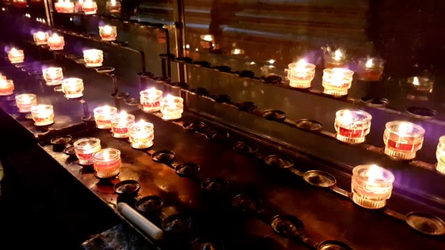 Votive candles standing on some racks in a Christian  Cathedral in Europ video