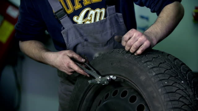 HD: Vulcaniser hammers a metal piece into the tire video
