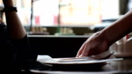 Waiter in a restaurant brings a delicious fresh salad dish to the table. video
