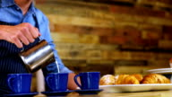 Waiter pouring milk in coffee at counter video