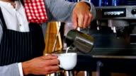 Waiter pouring milk in coffee video