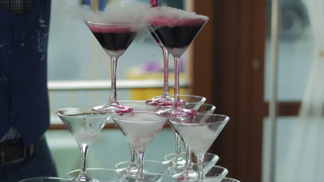 Waiter pouring red wine or champagne into glasses with liquid nitrogen for party. Young man pours wine into the pyramid from the glasses video