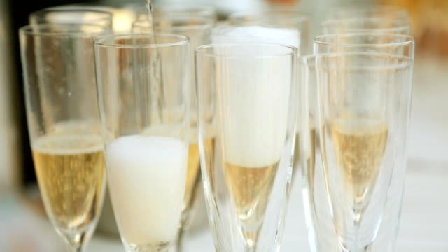 Waiter pours champagne into glasses video