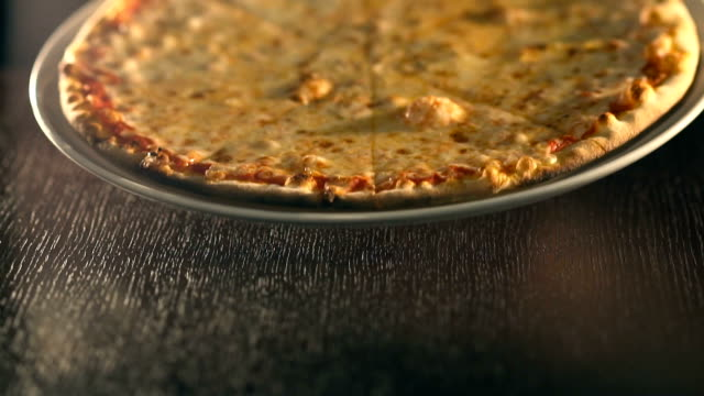 waiter puts ready tasty pizza on table. Slow Motion video
