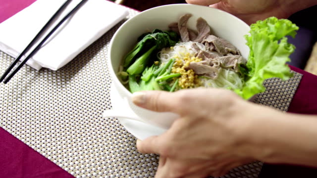 Waiter serve traditional Vietnam Pho Bo (beef noodle soup) in restaurant. video