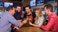 Waiter serving a group of friends at the bar video