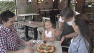 Waiter serving a pizza to a beautiful family at a restaurant video