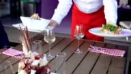 Waiter serving meal int restauran video