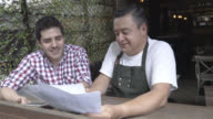 Waiter sharing ideas with business owner of a new menu video