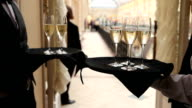 Waiters holds trays with glasses champagne on reception video