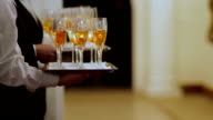 MEDIUM SHOT CLOSE UP Waiters with champagne flutes on trays video