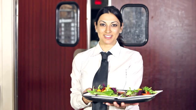 Waitress carrying food out of kitchen in restaurant video
