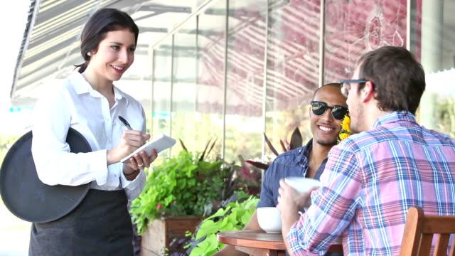 Waitress in sidewalk cafe taking customer orders video