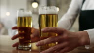 Waitress picking up two glasses of beer video