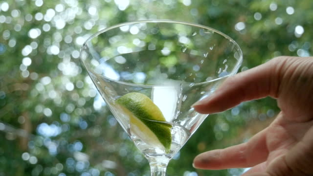Waitress Picks Up an Empty Martini Glass at an Outdoor Bar video
