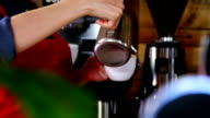 Waitress pouring milk in coffee at counter video