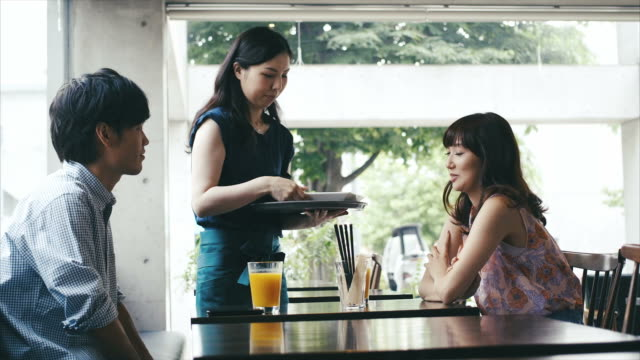 Waitress serves asian couple in cafe video