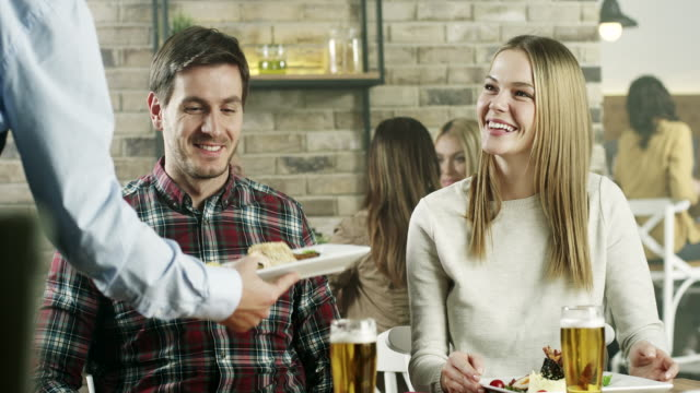 Waitress serving food to young couple video