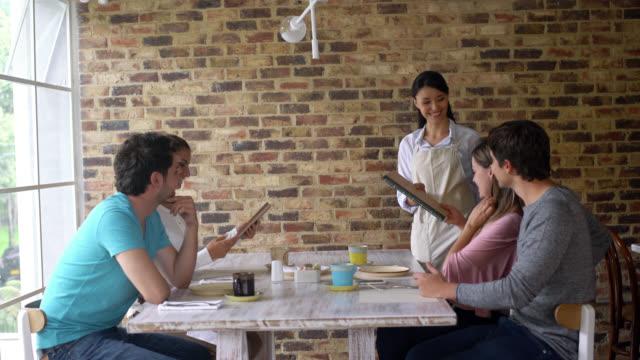 Waitress serving friends at a restaurant video