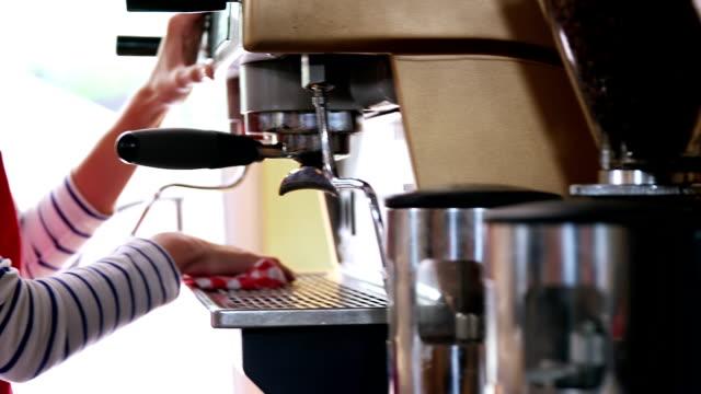 Waitress wiping espresso machine with napkin in café video