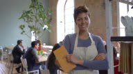 Waitress with arms crossed and holding a noted pad looking at camera video