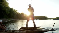 Wakeboarder in protection shoes start action on the board video