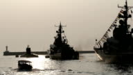 Walk along the warships in the harbor at sunset video